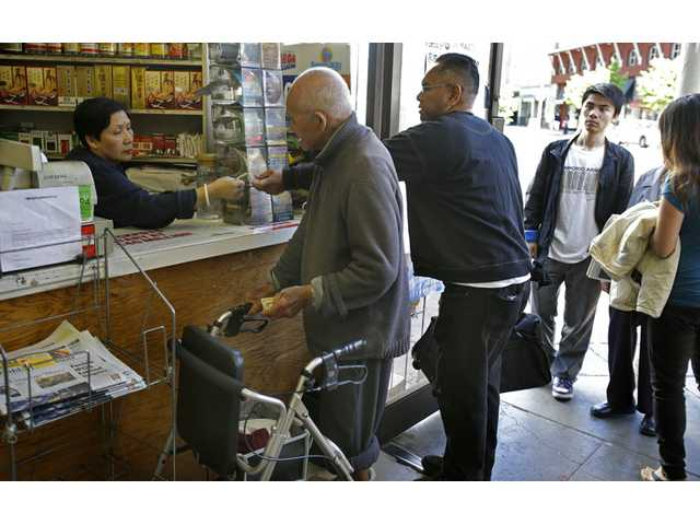 People line up to purchase Powerball lottery tickets on Saturday in the Chinatown district in Oakland.
