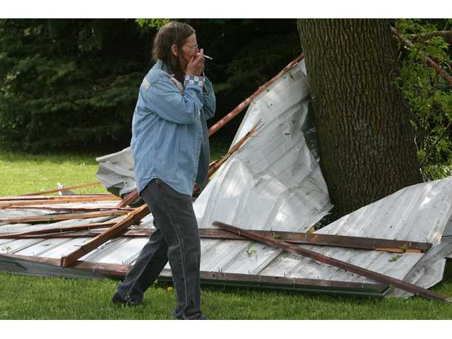 June McFarland reacts to the first sight of storm damage in rural Osage, Iowa on Sunday.