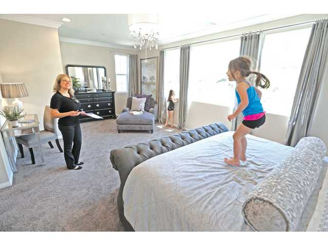 Kylie Macias, 3, jumps on the bed in the master bedroom of Residence Model 3 at Valle Di Oro, as Maria Mena of Coldwell Banker, left, looks on.