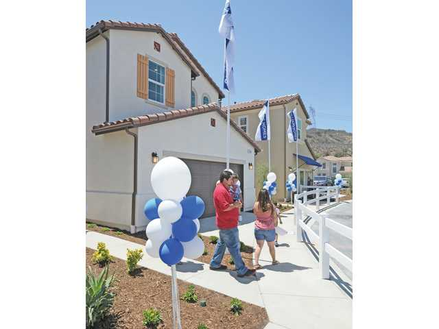 A family tours the model homes at Williams Homes - Valle Di Oro at the open house event in Canyon Country on Saturday.