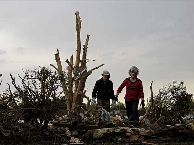 Lea Bessinger and her son Josh Bessinger look through the rubble of the elder Bessinger's tornado-ravaged home in Moore, Okla.