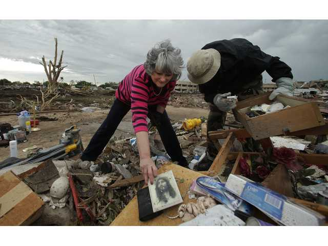 Lea Bessinger salvages a picture of Jesus as she and her son Josh Bessinger sort through the rubble of the elder Bessinger's tornado-ravaged home.
