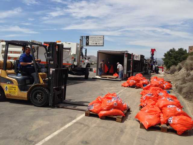 Workers continue to offload some of the 39,000 pounds of meat left in an overturned big rig on southbound Highway 14 south of Sand Canyon Road in Canyon Country.
