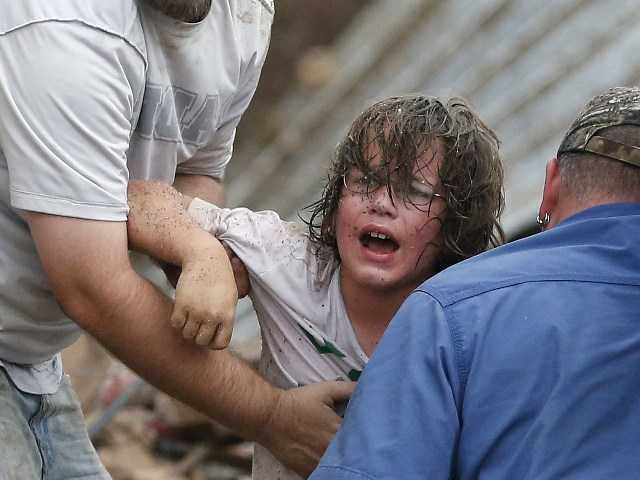 A child cries out to his father after being pulled from rubble at the Plaza Towers Elementary School in Moore, Okla.