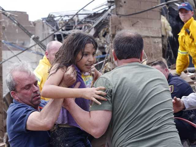 A child is pulled from rubble and passed along to rescuers at the Plaza Towers Elementary School in Moore, Okla.