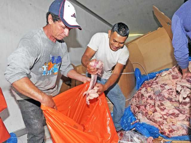 Manuel Polanco, left, and Eduardo Rosales offload some of the 39,000 pounds of meat left in an overturned big rig following a crash on southbound Highway 14 south of Sand Canyon Road in Canyon Country on Tuesday.