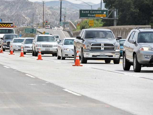 Traffic moves on two lanes of southbound Highway 14 near Sand Canyon Road as lanes were blocked following a big rig crash in Canyon Country on Tuesday.