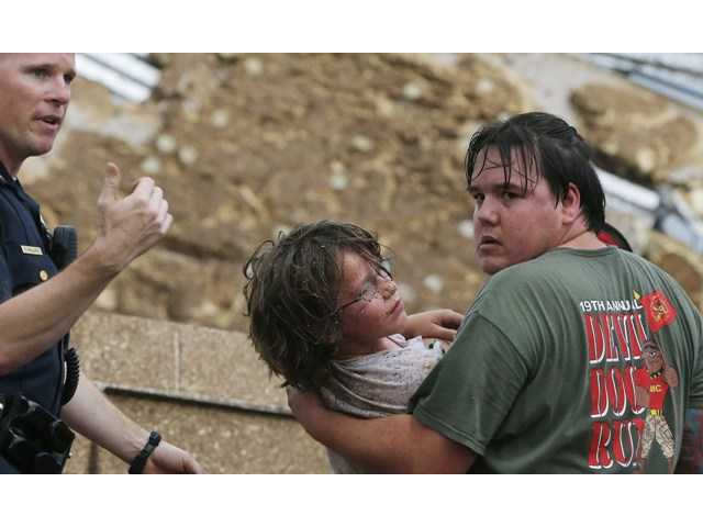 A child is carried from the rubble of the Plaza Towers Elementary School following a tornado in Moore, Okla., Monday, May 20.