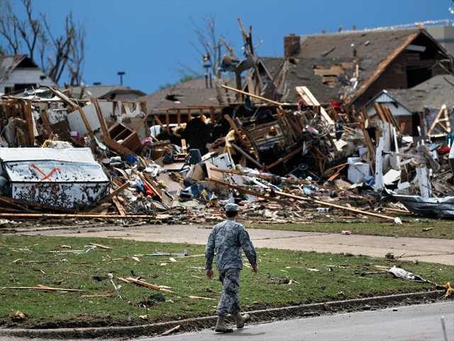 A soldier walks past the wreckage left when a tornado moved through Moore, Okla. on Tuesday.