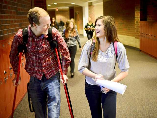 "Zach Sobiech walks with his girlfriend, Amy Adamle in 2012. Sobiech's song ""Clouds"" became an Internet sensation. He died early Monday from a rare form of bone cancer."