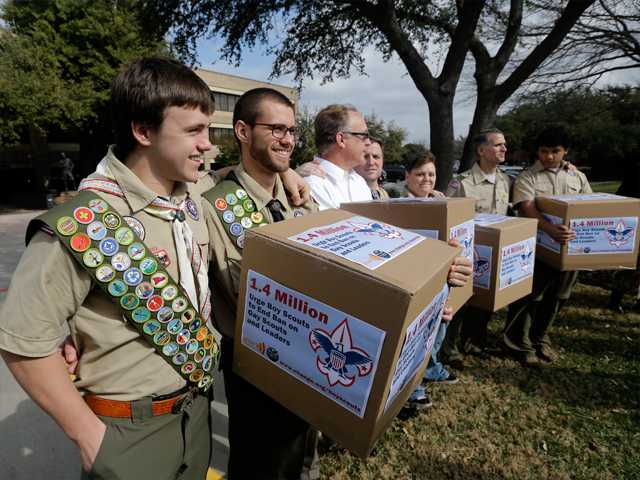 In this Feb., 2013 file photo, James Oliver, left, hugs his brother and fellow Eagle Scout, Will Oliver, who is gay, as Will and other supporters carry four boxes filled with petitions to end the ban on gay scouts and leaders in front of the Boy Scouts of America headquarters in Dallas, Texas.