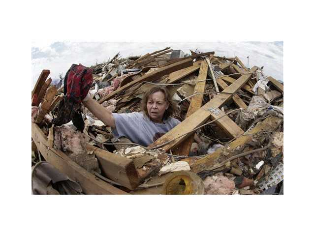 Carol Kawaykla salvages items at her tornado-ravaged home Thursday in Moore, Okla.