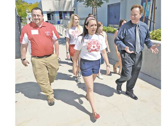 From left, Richard Lavoie, Gillian Lyons, and Gianna Zirpolo, from Saugus High School in Massachusetts, take a tour of Saugus High School in Saugus on Friday with Principal Bill Bolde.