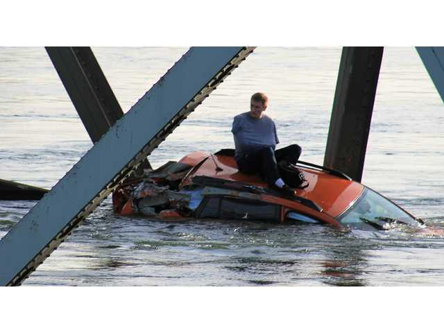 In this photo provided by Francisco Rodriguez, a man is seen sitting atop a car that fell into the Skagit River after the collapse of the Interstate 5 bridge minutes earlier Thursday in Mount Vernon, Wash.