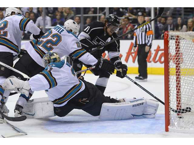 Los Angeles Kings center Anze Kopitar (11) pushes the puck across the goal line to score against San Jose Sharks goalie Antti Niemi (31) and defenseman Dan Boyle (22) on Thursday in Los Angeles.