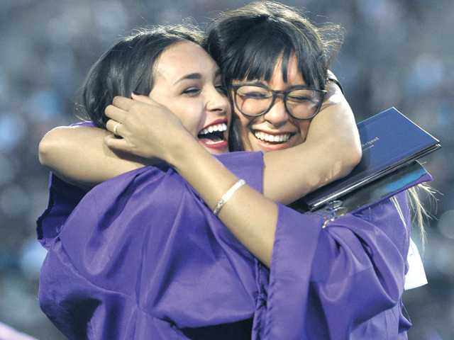 Desiree Pivovaroff, left, and longtime friend Rebecca Jacobik hug at the Valencia High School Graduation held at College of the Canyons in Valencia on Friday. Photo by Dan Watson
