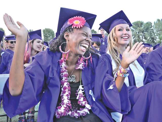 Tracy Adams, left, applauds during the Valencia High School Graduation held at College of the Canyons in Valencia on Friday.