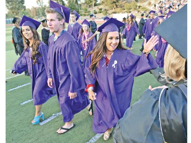 Breanna Argarin, right, high-fives the faculty members as the line the entrance at the Valencia High School Graduation held at College of the Canyons in Valencia on Friday. Photo by Dan Watson