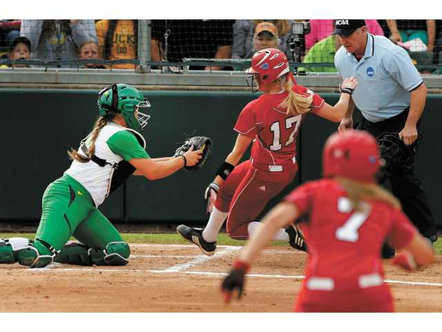 West Ranch graduate Janelle Lindvall and Oregon catcher reaches for the tag as Nebraska's Mattie Fowler tries to score in Game 1 of the Eugene Super Regional on Saturday. Nebraska eliminated Oregon in three games.