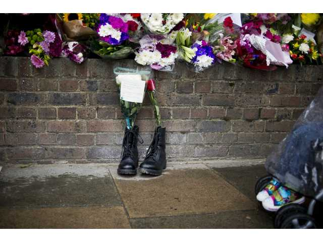 Military boots are laid in tribute outside the Woolwich Barracks, in London, in response to the bloody attack on Wednesday when a British soldier was killed in the nearby street.