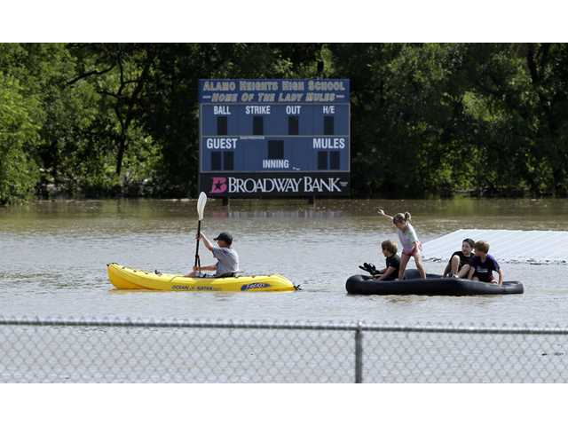 A kayaker pulls a raft with children around a flooded baseball park in San Antonio on Saturday.