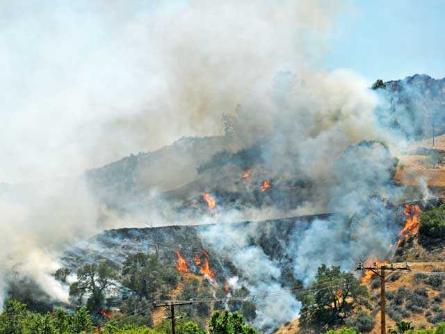 A brush fire burns through a hillside as seen from Del Valle Road in Val Verde on Monday. Signal photo by Jonathan Pobre