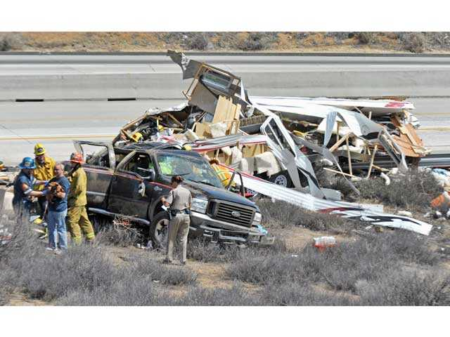 First responders work the scene of a crash involving a pickup truck and a trailer that flipped on its side on southbound Highway 14 north of Escondido Canyon Road in Agua Dulce on Monday. Signal photo by Jonathan Pobre