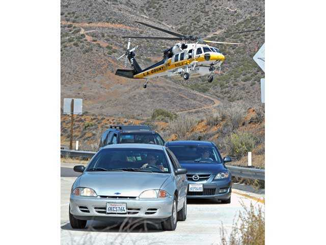 A Los Angeles County Fire helicopter is seen behind motorists exiting southbound Highway 14 at Escondido Canyon Road as it prepares to land on the roadway to transport patients involved in a crash in Agua Dulce on Monday. Signal photo by Jonathan Pobre