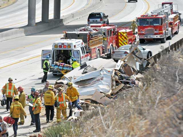 A patient is taken to an ambulance as firefighters and California Highway Patrol officers work the scene of a crash on southbound Highway 14 at Escondido Canyon Road in Agua Dulce. Signal photo by Jonathan Pobre