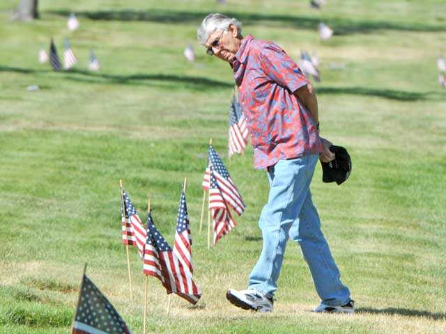 Bob Harris of Valencia walks past graves marked with American flags. Photo by Jonathan Pobre.