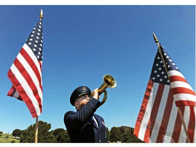 "Bugler Bruce Fischer plays ""Taps."" Photo by Jonathan Pobre."
