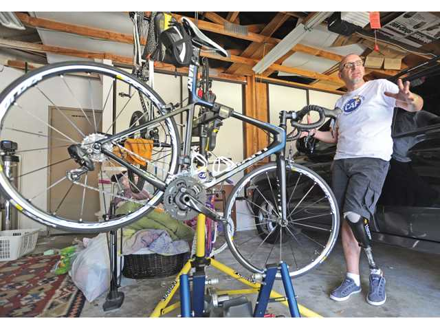 Kevin Korenthal stands in his garage with a couple of his bikes. Korenthal, an amputee, was hit by a car while biking, but just months later is training for a 620-mile bike race to raise money for challenged athletes. Photo by Dan Watson.