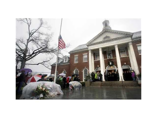 "In this Dec. 21, 2013 file photo, officials observe a moment of silence on the steps of Edmond Town Hall in Newtown, Conn. A comedy benefit event, ""Stand up for Newtown,"" is scheduled to be held at Town Hall on June 7, 2013."