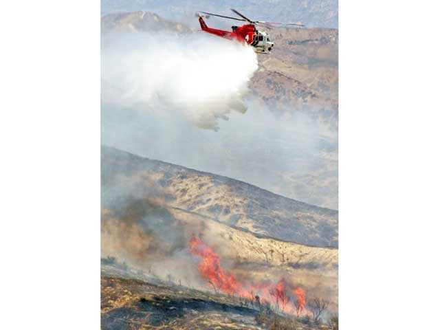 A Los Angeles City Fire Department helicopter makes a water drop over a fire as seen from Shadow Rock Lane in Westridge. Photo courtesy Jennifer Guerini.