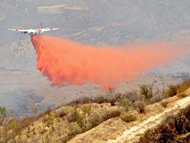 An aerial tanker drops retardant on a ridge behind Westridge Parkway. Photo by Rick McClure.