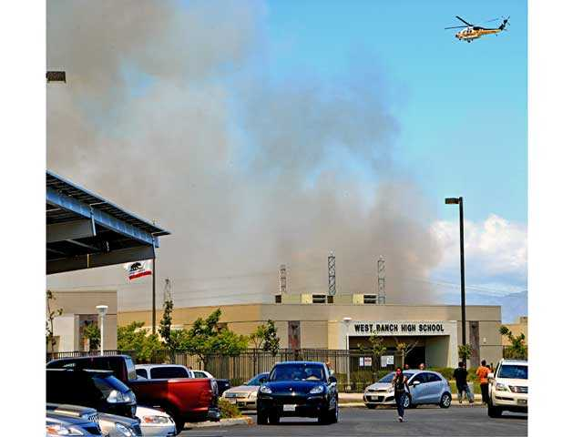 Smoke rises from behind West Ranch High School as an LA County Fire copter flies overhead. Photo by Rick McClure.