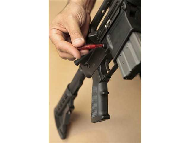 In this Aug. 15, 2012 file photo a plastic replica of a bullet is used to quickly remove an ammunition magazine from an assault rifle in a demonstration at the California Department of Justice in Sacramento. In response to the mass shootings in Connecticut and Colorado, California Legislators will vote on a package of gun control laws, including a bill to restrict the rapid reloading of weapons.