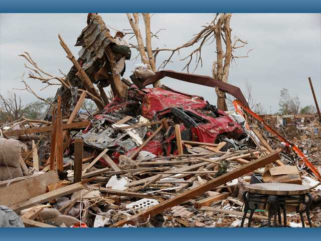 Two trees have become the resting place for twisted pieces of metal, a car and other tornado debris in Moore, Okla., on Monday.