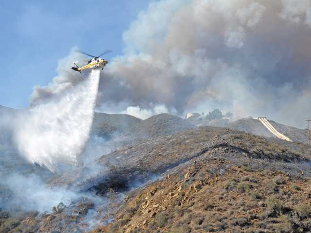 A helicopter performs a water drop on the Powerhouse Fire on Friday. The quick-moving fire charred 1,000 acres and forced evacuations in the Green Valley area.