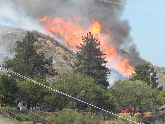 Open flames from the Powerhouse Fire are visible on Friday. The quick-moving fire has charred 1,000 acres and forced evacuations in the Green Valley area.