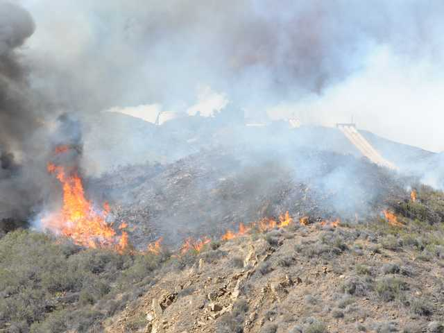 Open flames from the Powerhouse Fire are visible on Friday. The quick-moving fire charred 1,000 acres and forced evacuations in the Green Valley area.