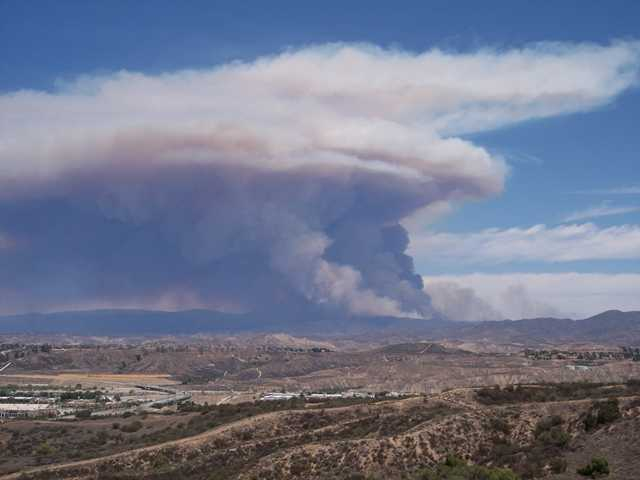 This photo, taken from the parking lot of Golden Valley High School, shows the plume of smoke rising from the still-burning Powerhouse Fire.