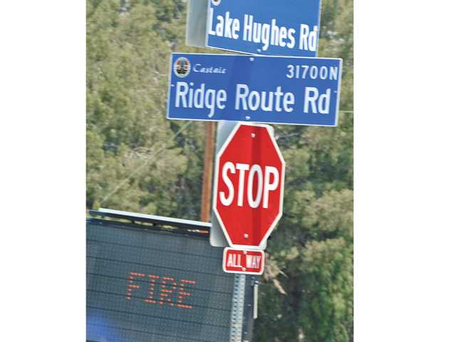 "An electronic sign reads ""fire"" at the corner of Lake Hughes Road and Ridge Route Road. Lake Hughes Road was closed Saturday due to the Powerhouse Fire burning north of the Santa Clarita Valley. Dan Watson/The Signal"