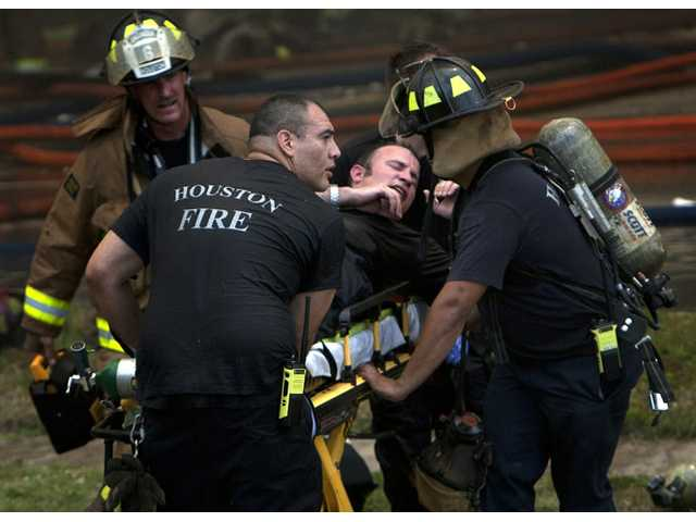 A firefighter is wheeled to an ambulance after fighting a fire at the Southwest Inn on Friday in Houston.