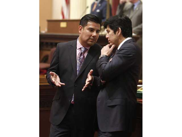 In this photo taken Wednesday state Sen. Ricardo Lara, D-Bell Gardens, left, talks with Sen. Kevin de Leon, D-Los Angeles, during the Senate session at the Capitol in Sacramento.