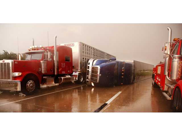 A truck squeezes past an overturned tractor-trailer on I-40 west of Banner Rd. Friday in El Reno, Okla.