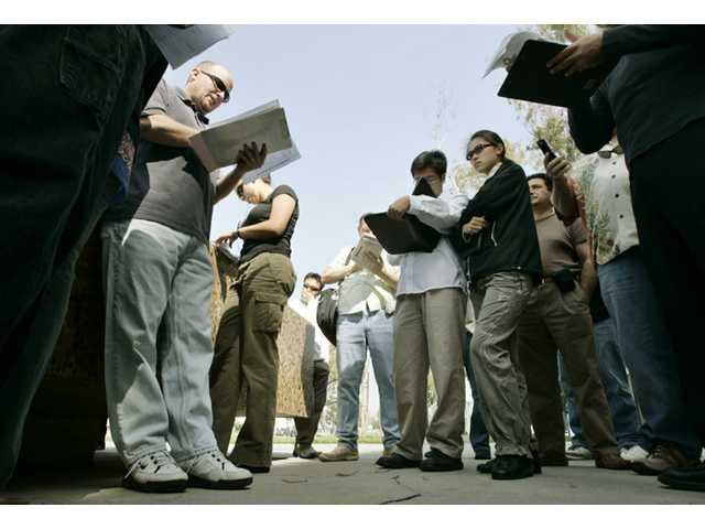 Travis Toth, left, an auctioneer of trustee sales for Fidelity National, reads descriptions of foreclosed properties offered for sale as potential buyers contemplate bids during a home foreclosure auction on the steps of the Los Angeles County courthouse in Norwalk, Calif., in March 2007.