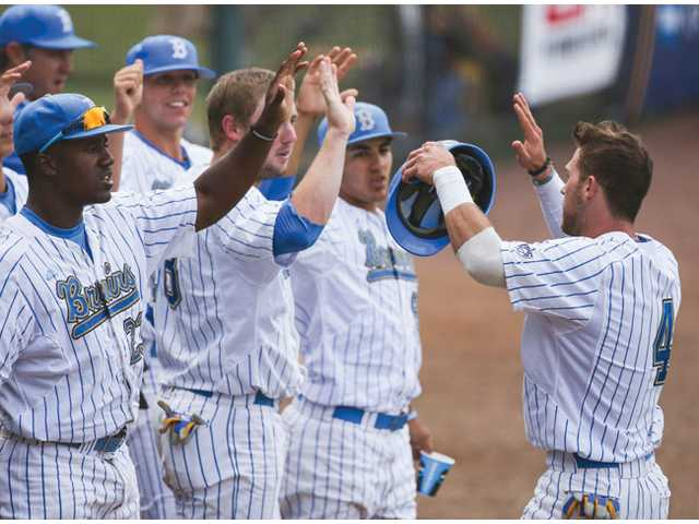 UCLA's Eric Filia, right, celebrates scoring a run with his teammates against San Diego on Sunday in Los Angeles.