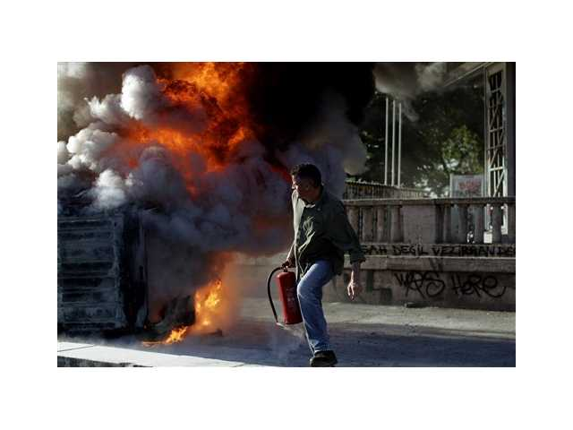 A protester holding a fire extinguisher moves away from a burning car during a protest at Taksim Square in Istanbul, today. Demonstrations that grew out of anger over excessive police force have spiraled into Turkey's biggest anti-government demonstrations in years, challenging Prime Minister's Recep Tayyip Erdogan power.