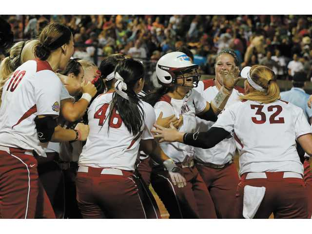 Oklahoma infielder Lauren Chamberlain, in center with batting helmet, is mobbed by her teammates following her 12th-inning, walk-off home run against Tennessee in the Women's College World Series in Oklahoma City on Monday.